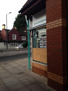 Boarded up: the damaged window at Anne James Estate Agents; behind is the Harvester pub which was also attacked