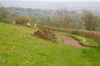 Workmen are creating a temporary footpath in the field above the landslip which will open up access for the first time in over two months