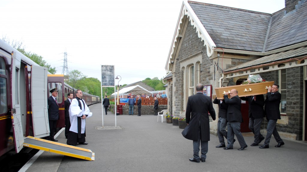 Bob' Hitchings' coffin is carried through the booking office to the waiting train