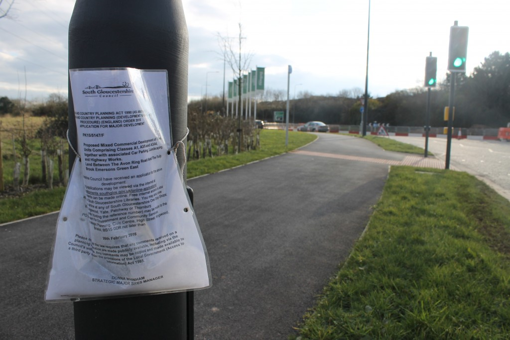 A sign giving notice of the proposed development is on a post near the roundabout